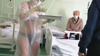 Photo of Nurse who only wore underwear under transparent PPE gown on male hospital ward in Russia because she was 'too hot' is disciplined (but the patients don't seem upset!)